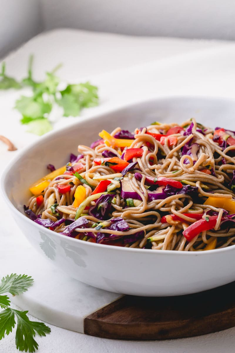 This Asian noodle salad is made with nutty soba noodles and rainbow of vegetables. Bursting with Asian flavors, this light, flavorful and healthy side dish is a perfect addition to any BBQ dish! #asiannoodlesalad #noodlesalad