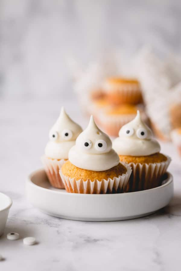 3 mini pumpkin muffins on a white plate topped with domed cream cheese frosting and candy eyes.