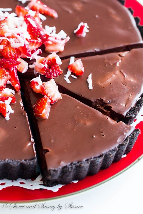 Every bite of this no-bake chocolate truffle tart, filled with fresh strawberries and coconut, literally melts in your mouth! It's chocoholic's dream tart.