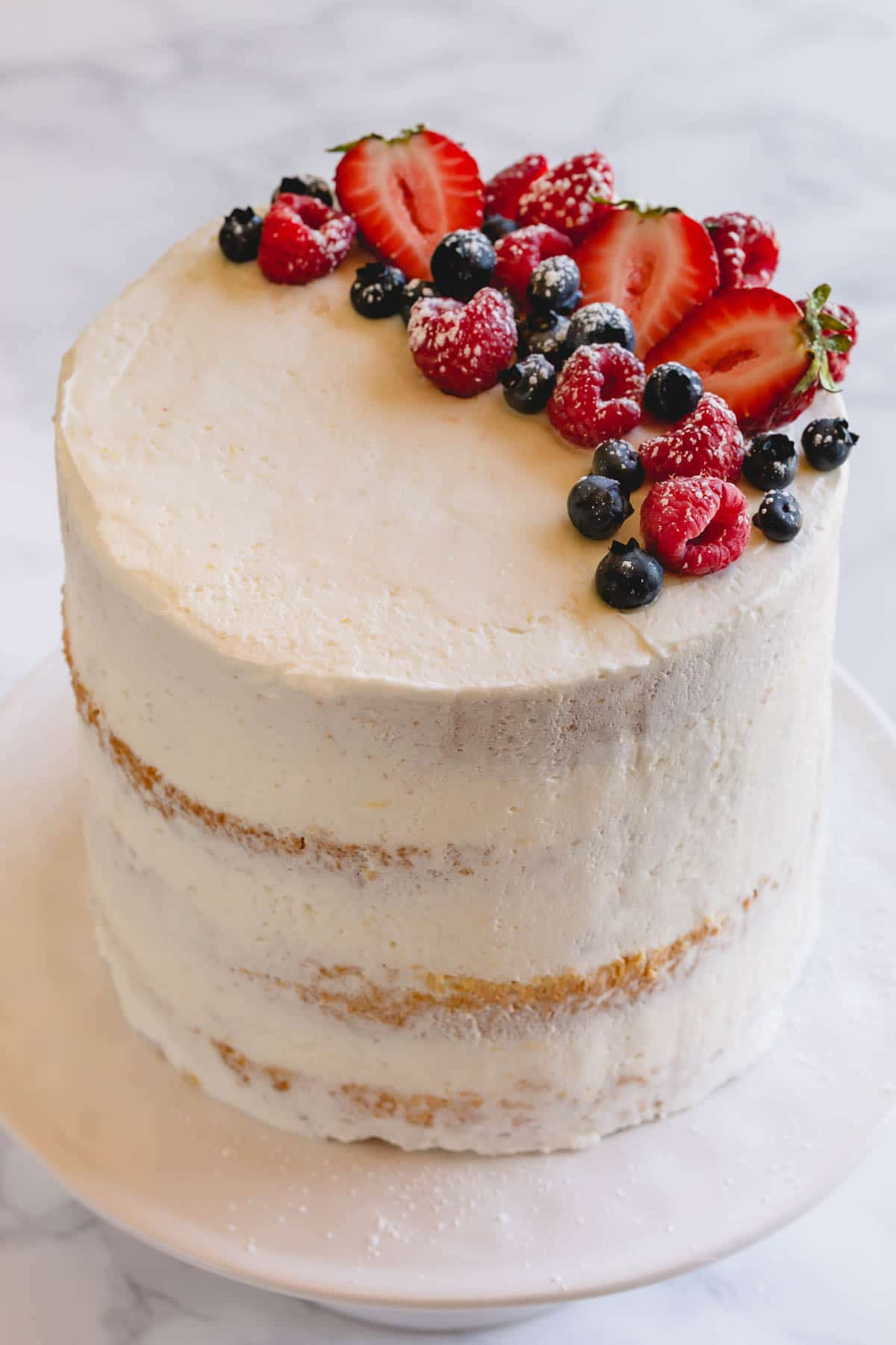 A 4-layer cake topped with fresh berries and with a slice cut out.