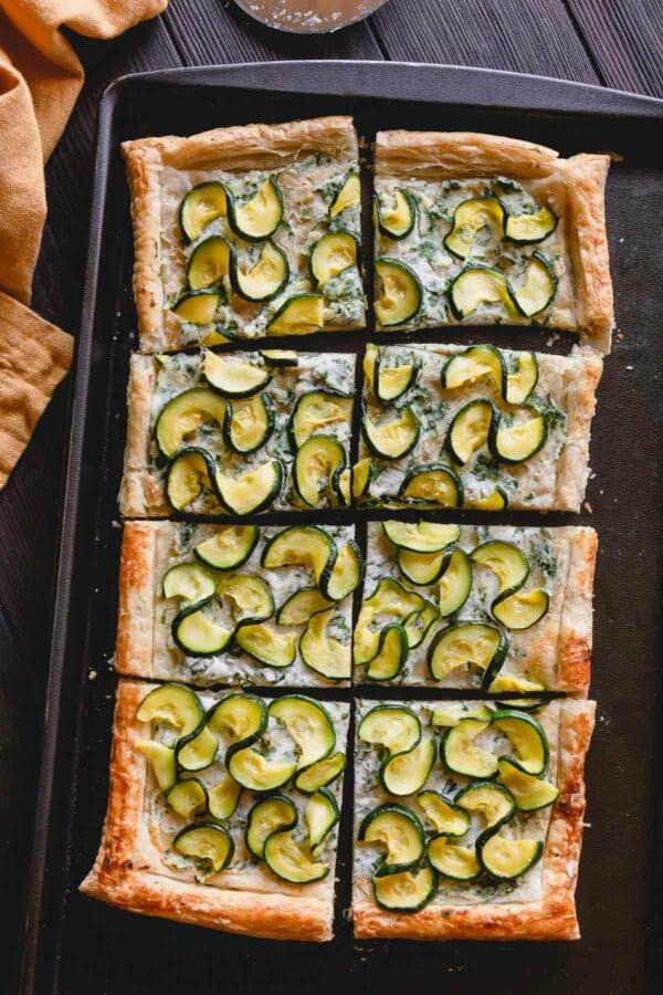Overhead shot of zucchini tart on a baking sheet.