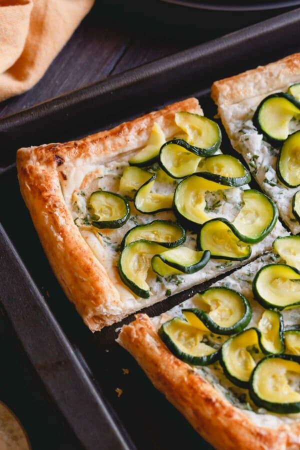 a close-up shot of zucchini tart on a baking sheet.