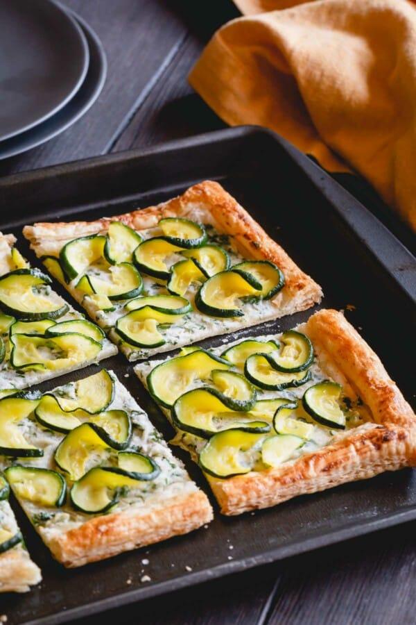Sliced zucchini tart on a baking sheet.
