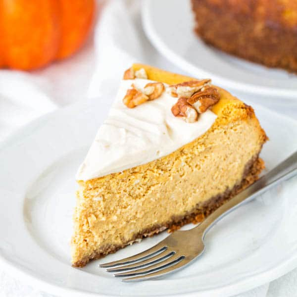 A slice of pumpkin cheesecake with maple pumpkin whipped cream frosting.