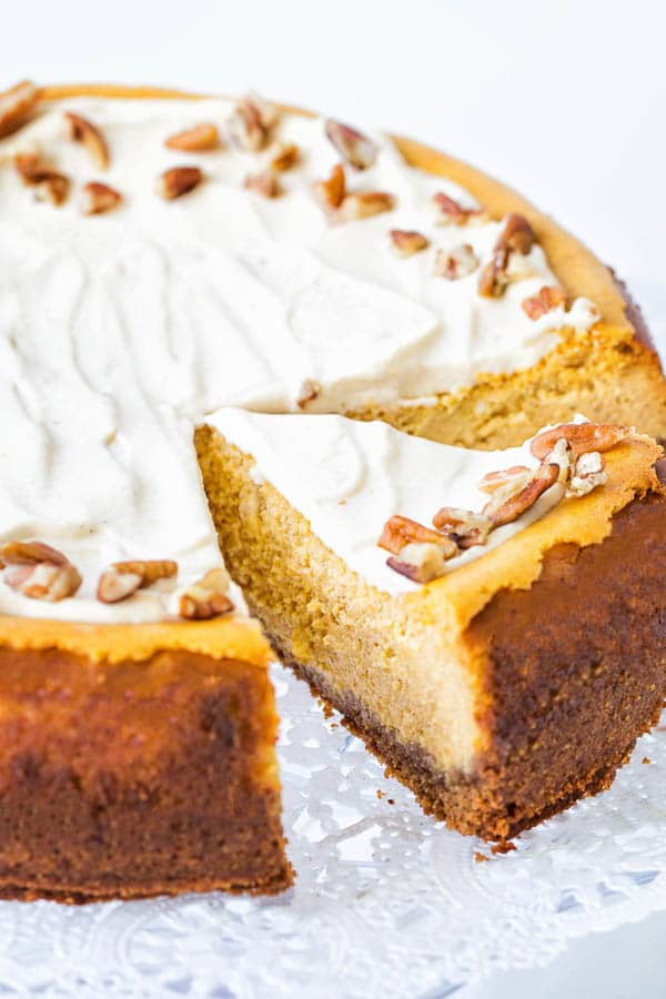 Creamy maple pumpkin cheesecake - a whole cake with one slice cut.