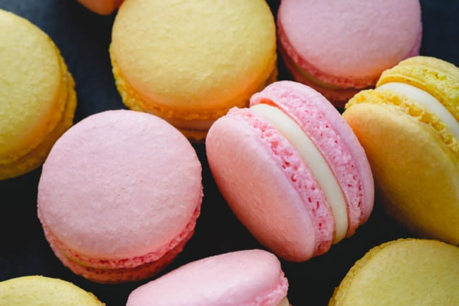 Yellow and pink macarons filled with white chocolate ganache arranged on a dark surface