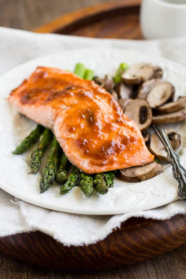 Spicy apricot salmon with roasted asparagus and mushrooms - light and nutritious dinner bursting with flavor! All it takes is one sheet pan, five ingredients, and less than 30 minutes! Quick n' simple doesn't have to be bland.