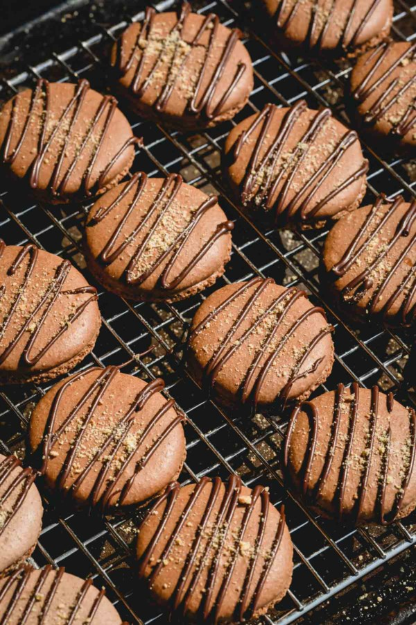 Chocolate macaron shells on a wire rack and drizzled with chocolate.