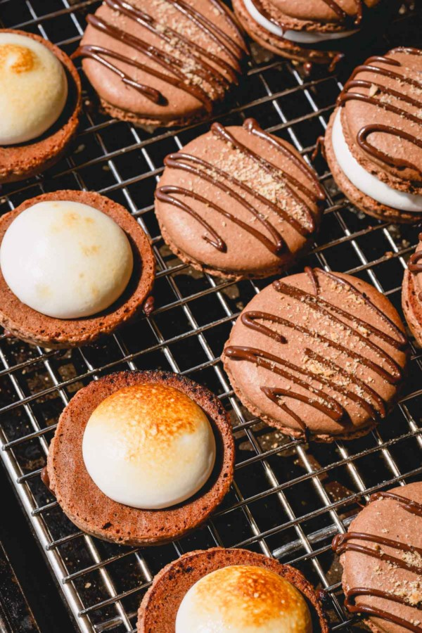 Chocolate macaron shells on a wire rack with a dollop of marshmallow filling.