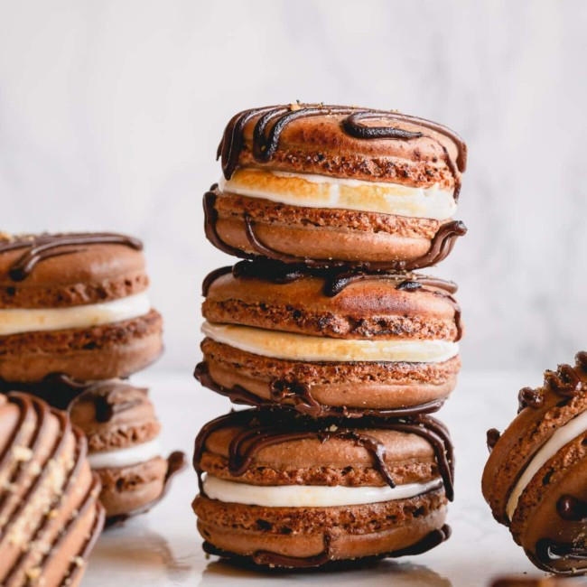 Filled s'mores macarons arranged on a counter.