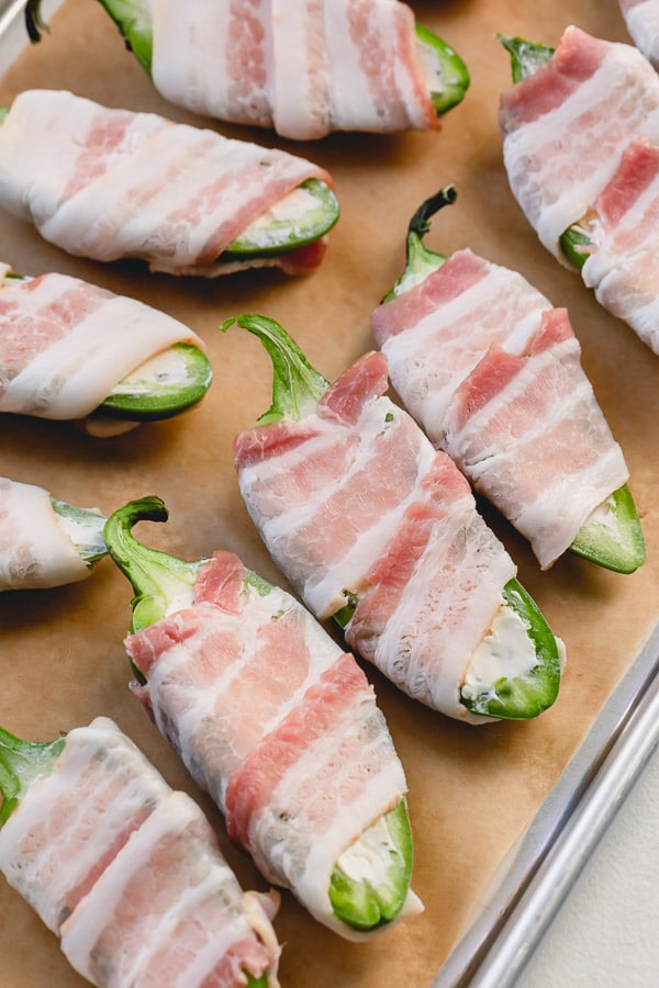 Step by step photo tutorial to make these addicting bacon wrapped jalapeno poppers. #jalapenopoppers #baconjalapenopoppers