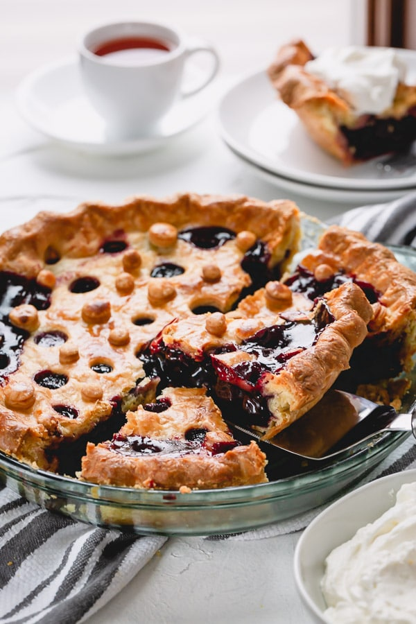 Homemade cherry pie with buttery flaky crust and thick cherry filling is easier than you may think! Besides my tried and tested recipe, you'll learn 3 tips to avoid runny cherry pie filling and an easy way to make a fun pie crust design. #cherrypie