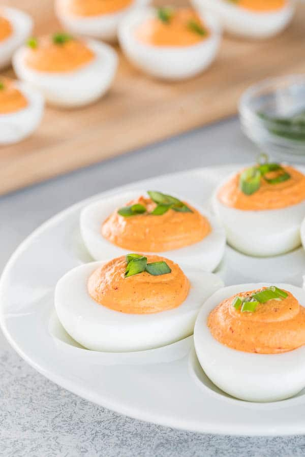 Roasted red pepper deviled eggs with ultra-smooth, creamy filling. The classic deviled egg recipe with big bold flavors and a spicy kick! #roastedredpepper #deviledeggs #easyappetizer