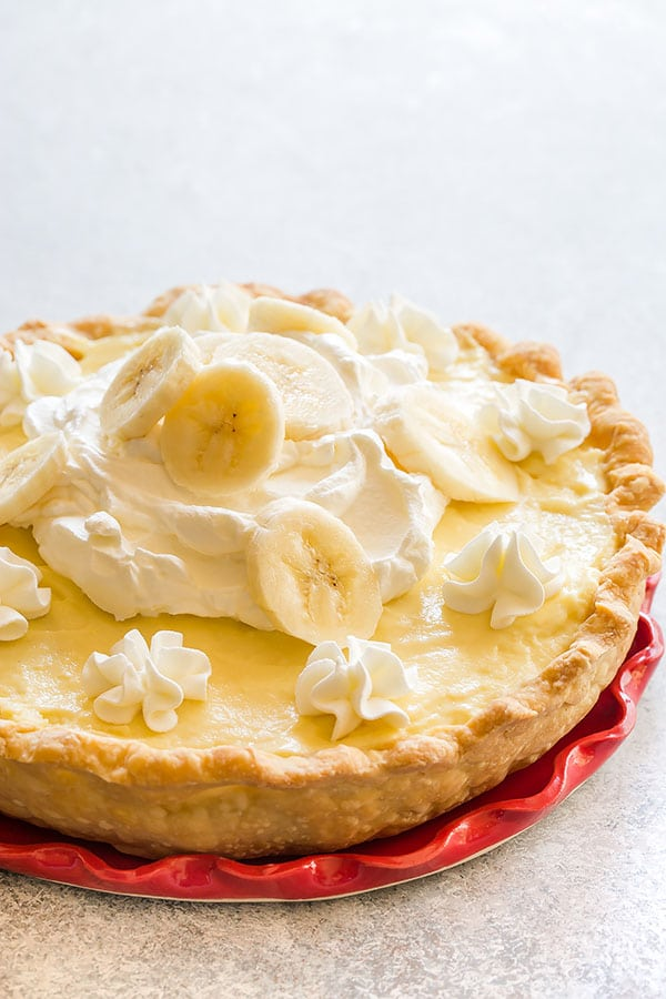 All-American, old-fashioned, 100% from scratch banana cream pie featuring flaky buttery pie crust, silky smooth vanilla pudding, plenty of bananas and homemade whipped cream. Seriously so delicious and can totally be prepared in advance! #bananacreampie #homemadepie #pie #homemadevanillapudding #piecrust