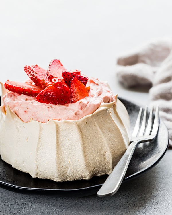 Dreamy, creamy and oh-so-delicate strawberry mini Pavlova is light and sweet mini desserts to impress your guests! Equipped with my top 5 tips and simple ingredients, you'll make perfect Pavlova every time. #minipavlova #pavlovacake #bakingtips #easydessert #impressivedessert