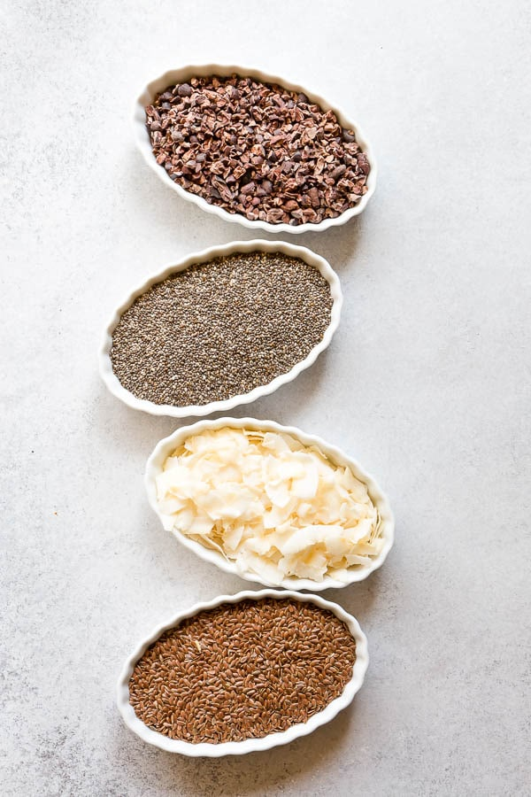 Variety of healthy toppings for fun yogurt bowls. Cocoa nibs, chia seeds, coconut chips and flax seeds! #yogurtbar #snack #healthysnack #snacktime #yogurtbowl