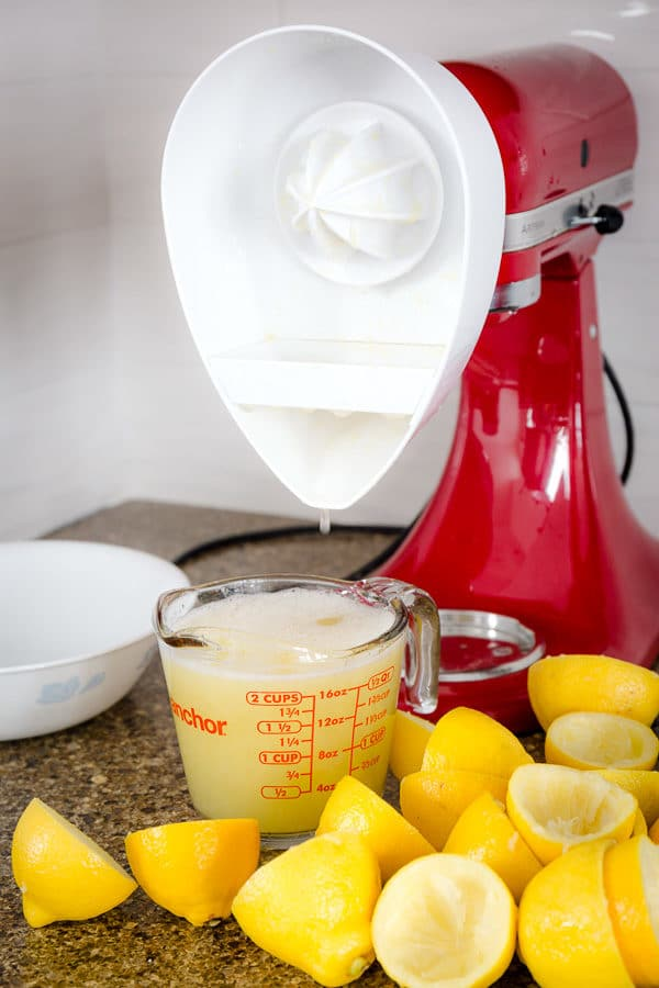 Stand mixer with citrus juicer attachment and glass of fresh lemon juice.