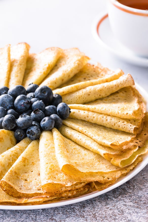 Here's my go-to basic crepe recipe for delicately thin and lacy crepes. All you need 8 simple ingredients and tried and tested tips for making perfect crepes every time! How-to video is included. #homemadecrepes #crepes