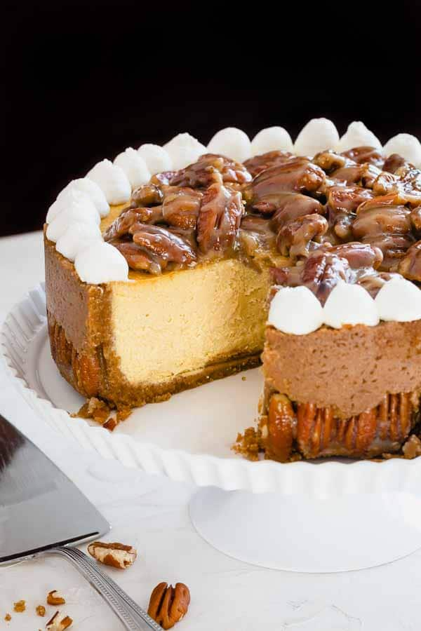 Incredibly indulgent, this pecan pie cheesecake consists of buttery nutty crust, super tall New York-style cheesecake and rich pecan pie topping! A perfect centerpiece for your holiday dessert table. #cheesecake #pecanpiecheesecake #ThanksgivingDessert
