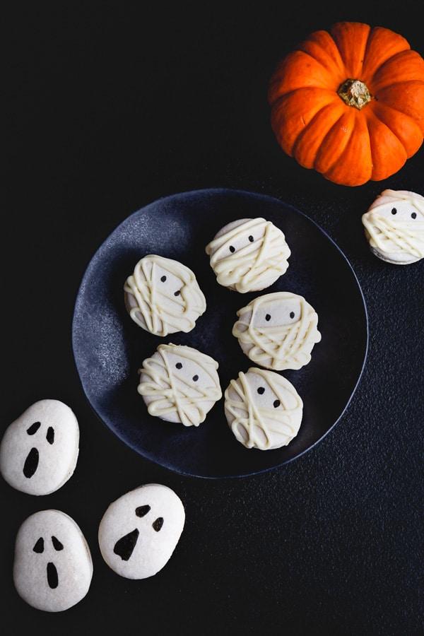 Spooky halloween macarons: mummy macarons and ghost macarons. #halloween #halloweendesserts #halloweenmacarons
