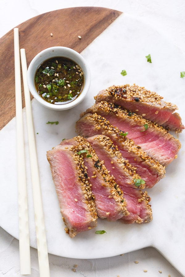 Sesame crusted seared Ahi tuna is one of those effortless dishes that never fails to impress. It's elegant and makes quite the presentation, but is simple enough for a weeknight meal in under 10 minutes! #ahituna #ahitunasteaks #tunasteaks #seafood