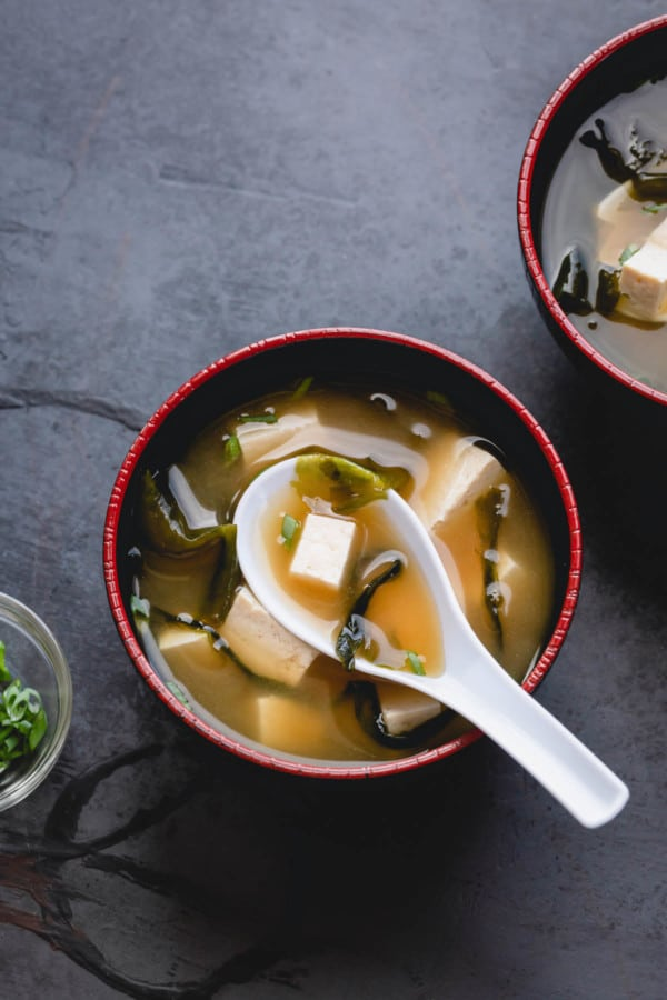 A bowl of miso soup with diced tofu and seaweed.