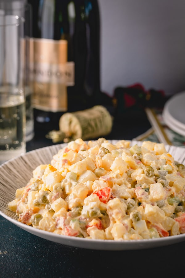 Olivier Salad, or Russian potato salad, is a meal on its own. Loaded with lots of vegetables, meats and eggs and finished with creamy mayo, this Russian salad is so satisfying and filling!  #russiansalad #russianpotatosalad #oliviersalad