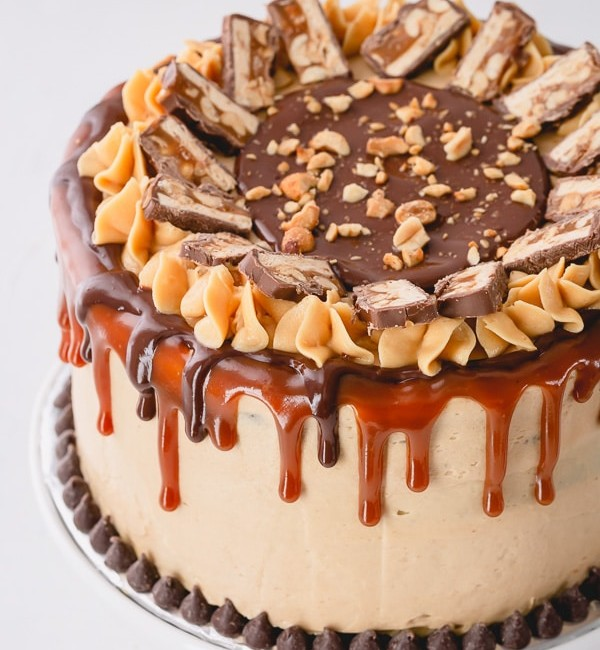 This irresistible Snickers Cake is made of layers of softest chocolate cake, caramel buttercream, peanut butter buttercream, salted caramel and generous amount of crushed peanuts!!! Step by step photos are included for your success! #snickerscake #layercake