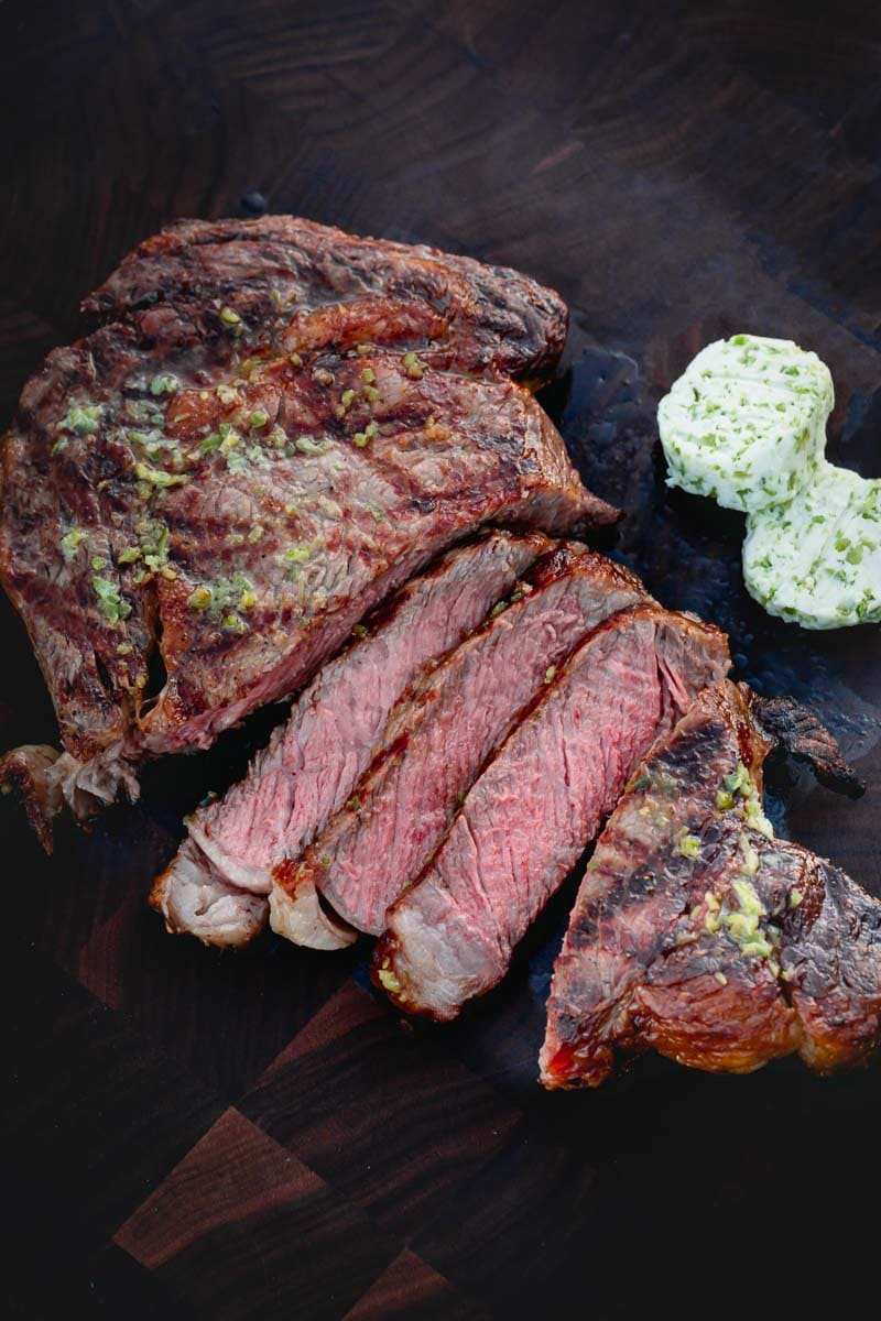 Sliced grilled steak on a wood cutting board with compound butter on the side