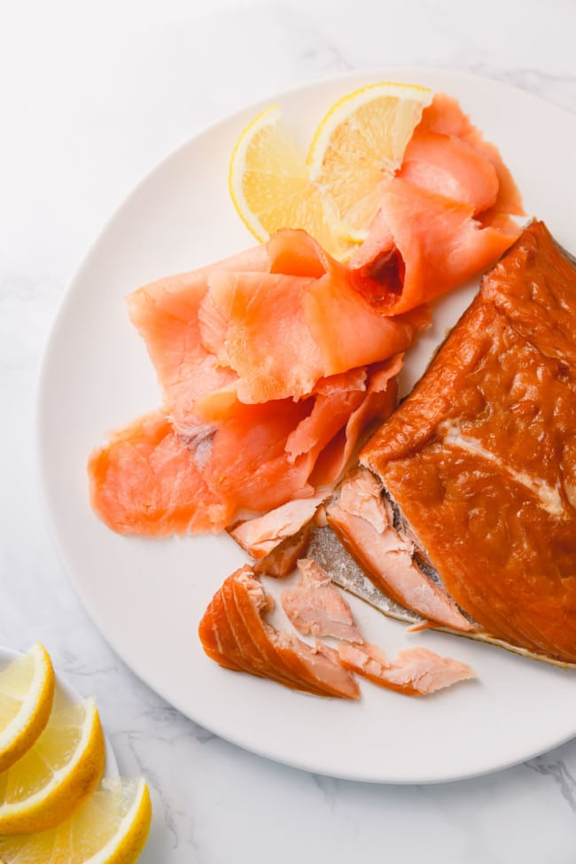 Hot smoked and cold-smoked salmons with couple of slices of lemon on a white plate. There're 2 types of smoked salmon: cold-smoked and hot smoked.