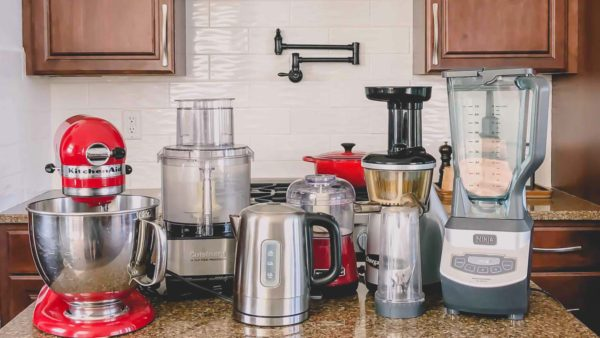 My absolute favorite small kitchen appliances are lined up on a the counter - kitchenaid stand mixer, cuisinart food processor, electric water kettle, small chopper, juicer and blender.