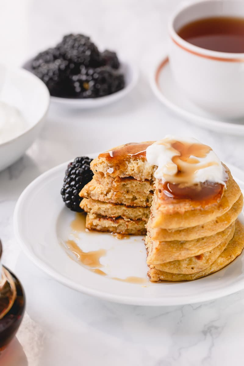 stack of banana pancakes on a plate with a quarter of the pancakes slices out