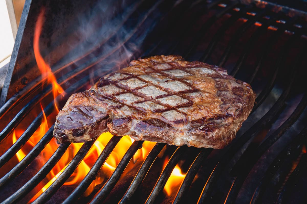 A ribeye steak on gas grill over a flame