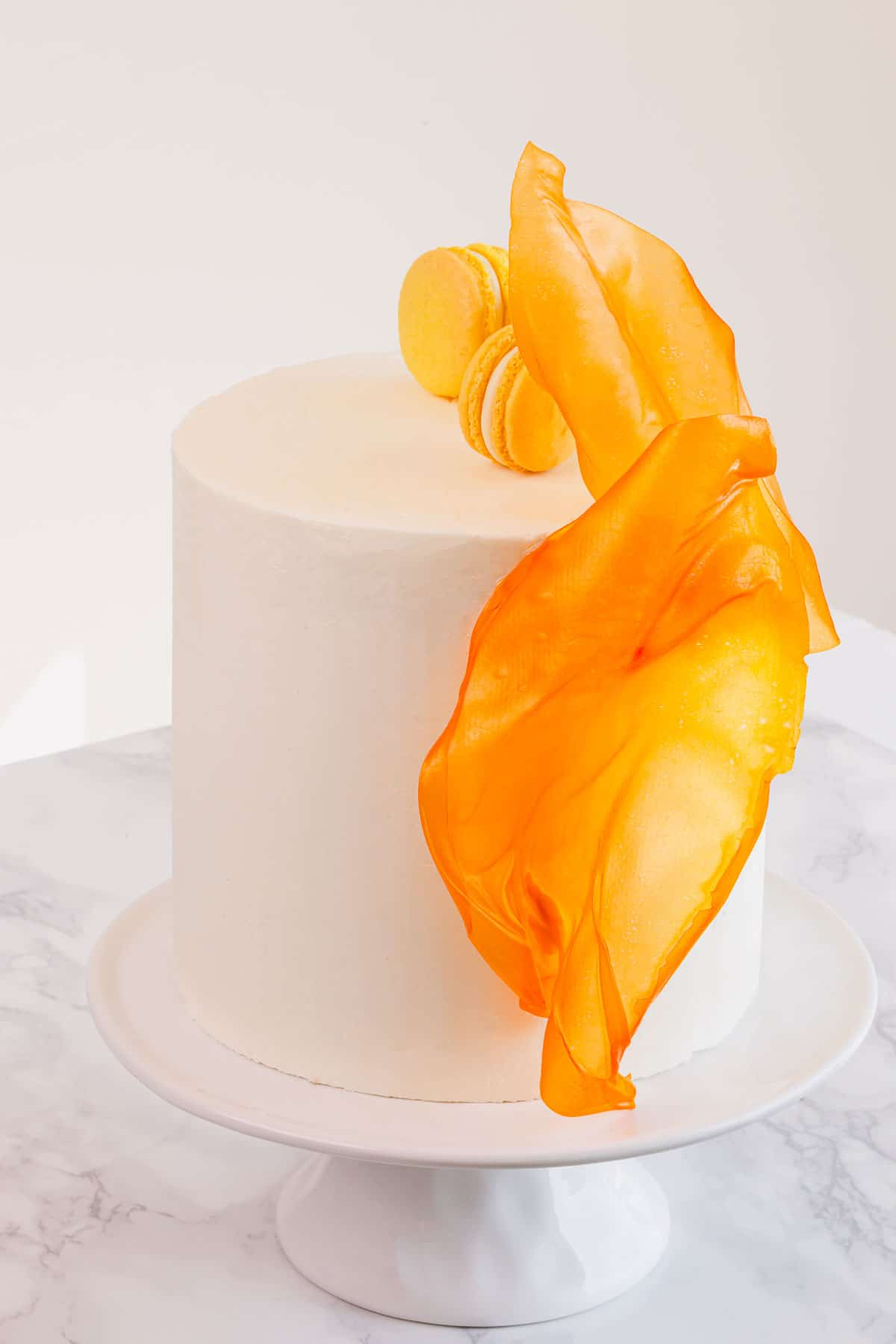 Tall white layer cake decorated with orange rice paper sails and macarons on a cake stand.
