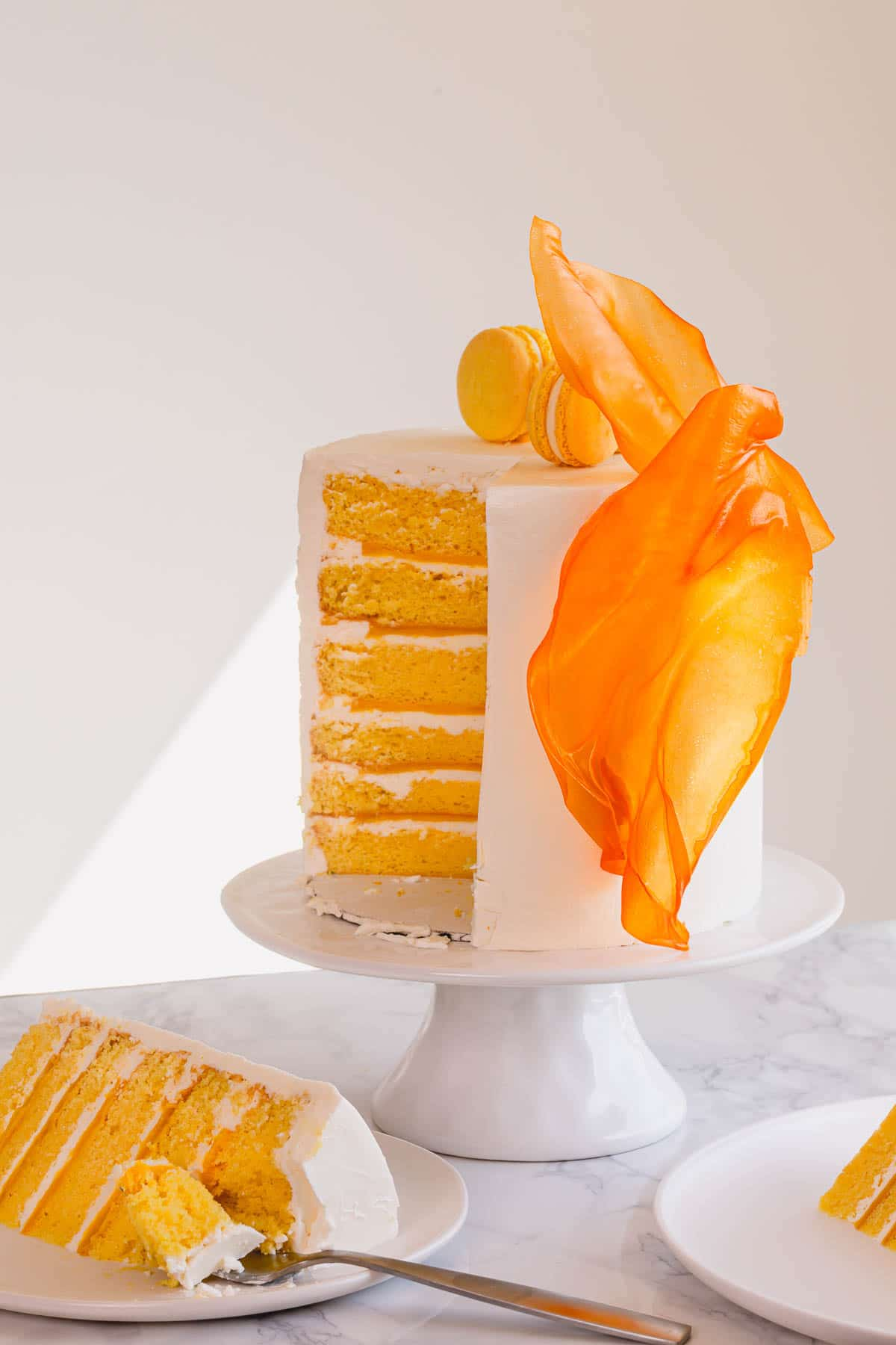 A tall cake on cake stand & slice of cake on plate with fork