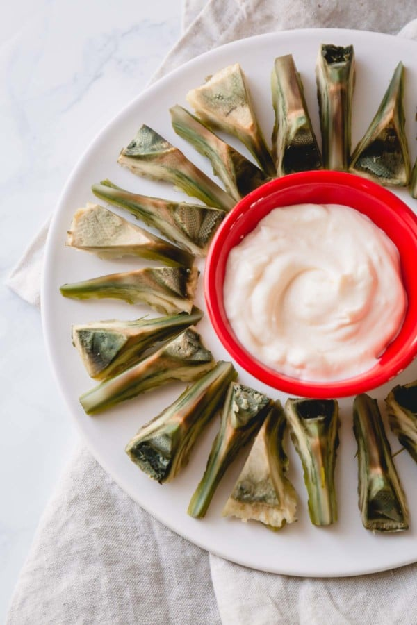 Sliced artichoke heart with a dipping sauce on a serving platter.