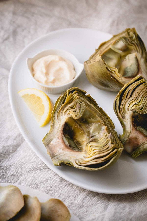 boiled artichoke halves served with a wedge of lemon and dipping sauce on a white plate