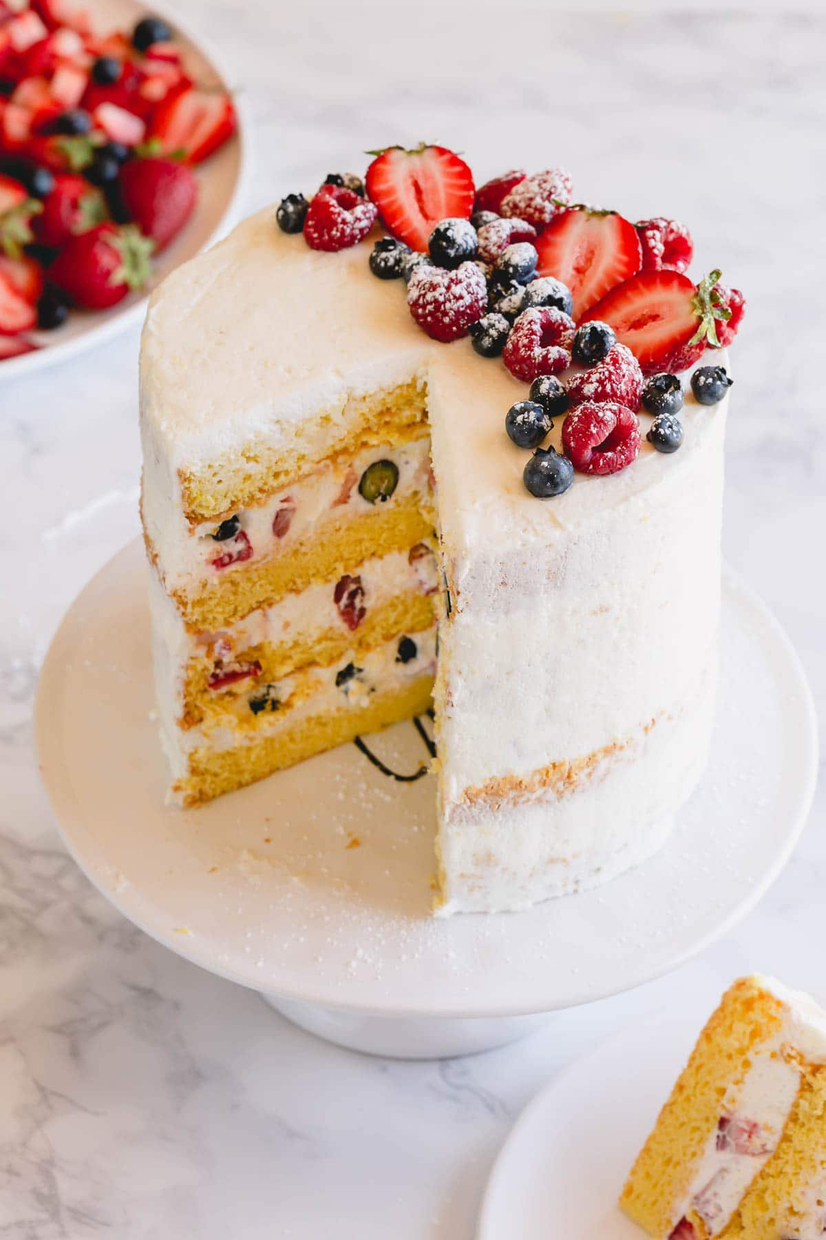 A tall 4-layer cake topped with berries on a cake platter.