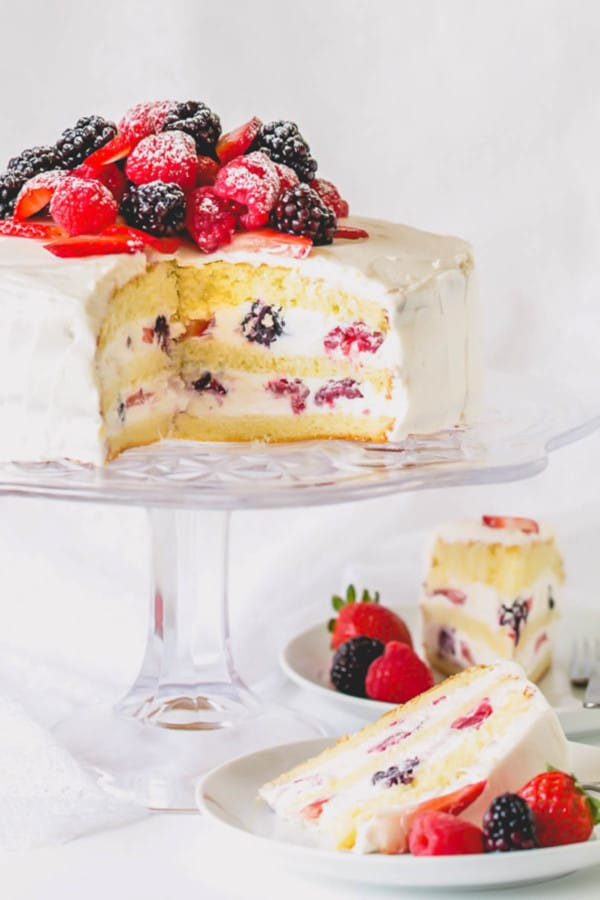 Berry Chantilly cake on a cake platter and a slice on a plate.