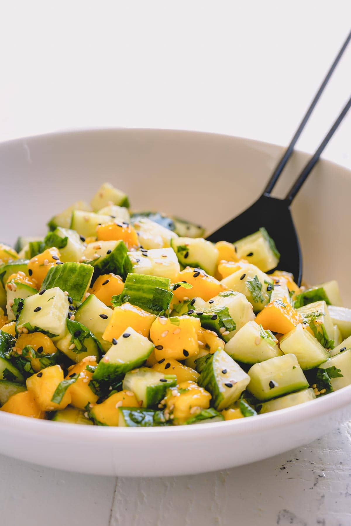 Cucumber mango salad in a white salad bowl.