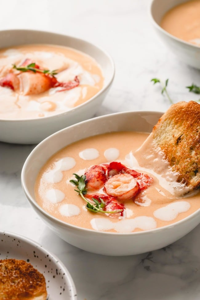 Lobster Bisque in bowl with bread stick