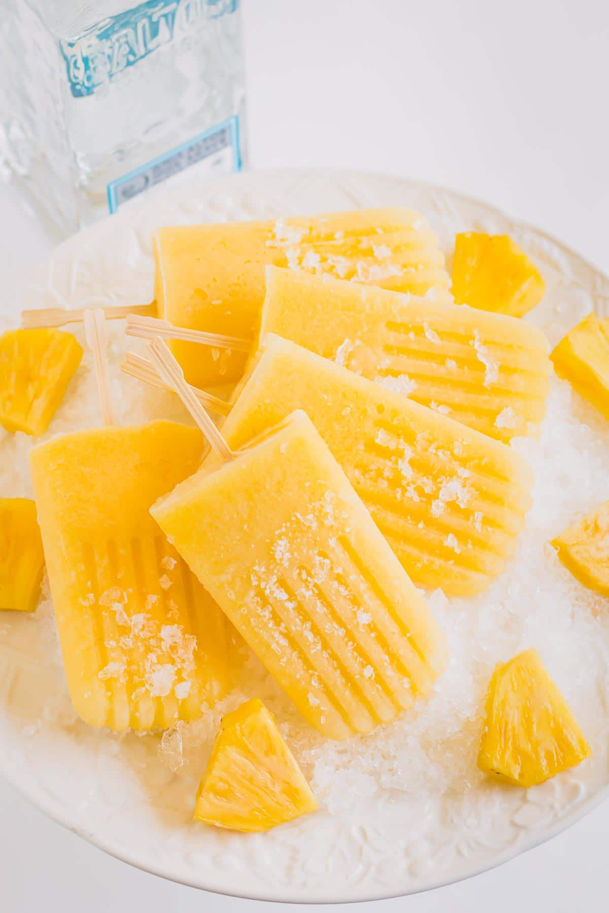 Handful of pineapple popsicles on crushed ice.