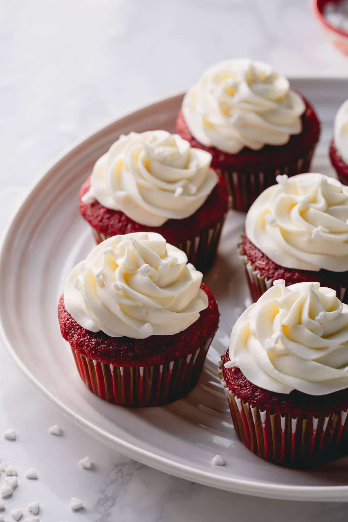 Half a dozen red velvet cupcakes frosted with cream cheese frosting