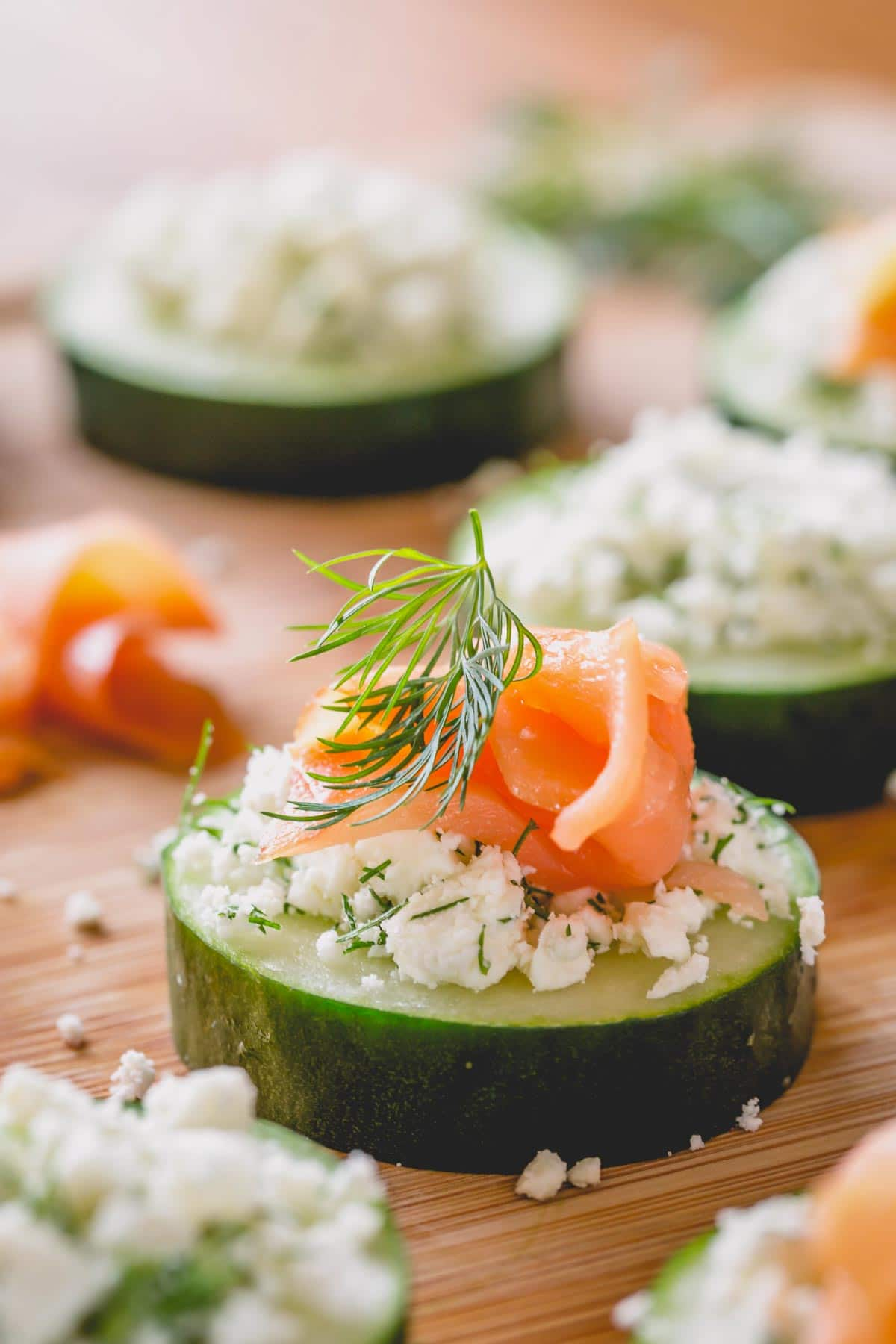 A cucumber slice topped with feta cheese, dill and salmon on a wooden serving platter.
