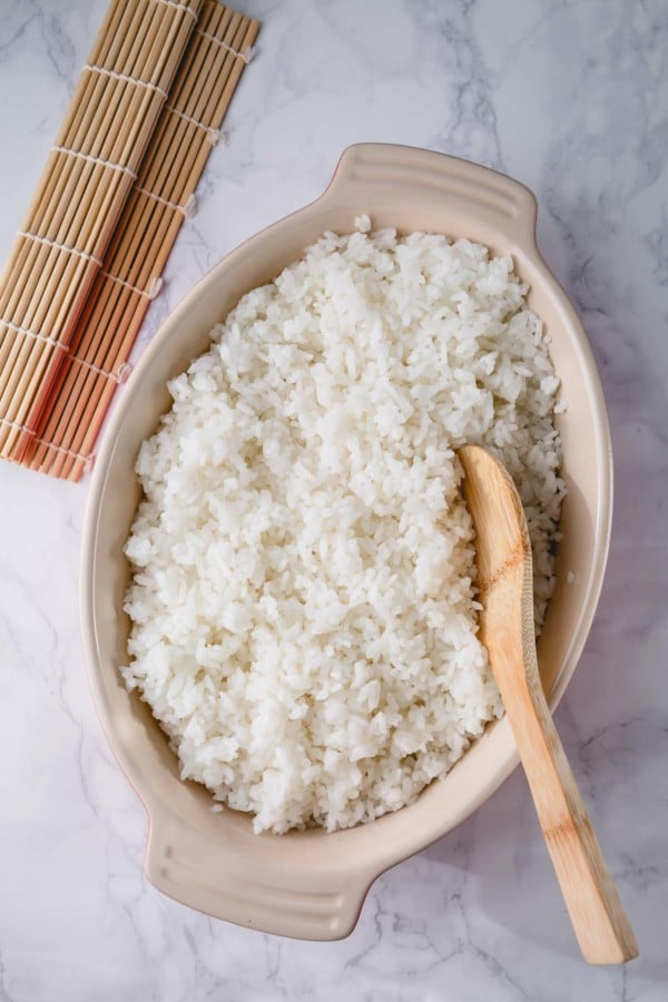 sushi rice serve in a dish with a wooden spoon