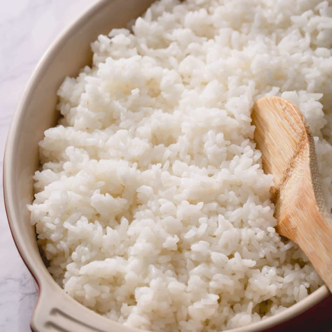 sushi rice in a dish with a wooden spoon