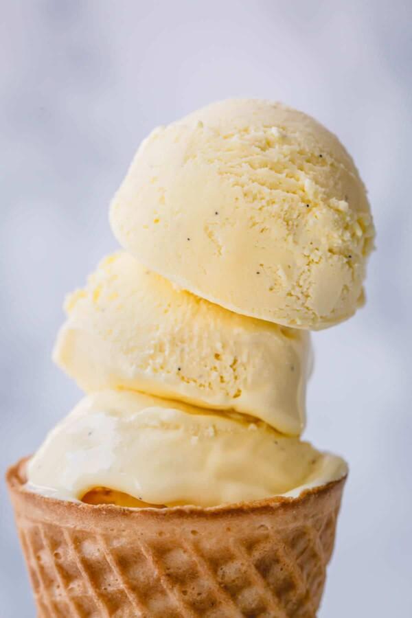 three vanilla ice cream scoops stacked on wafer cone.