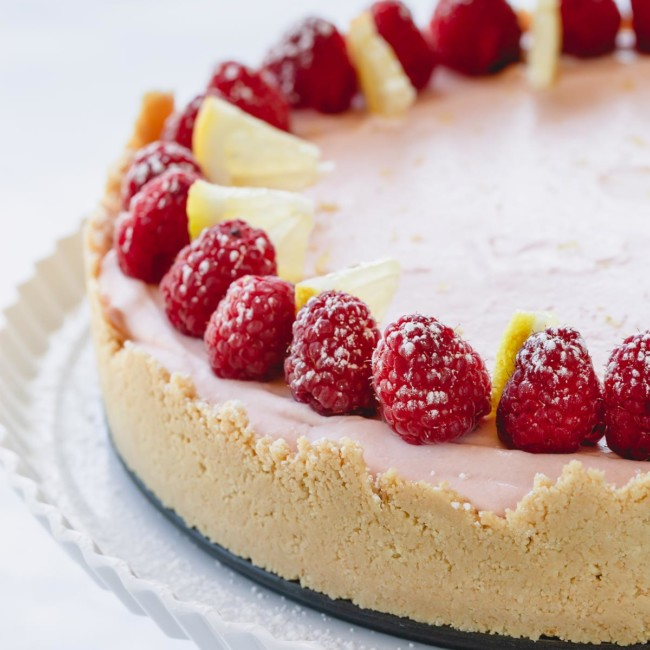 a whole lemon raspberry cheesecake topped with fresh raspberries on a white serving platter.