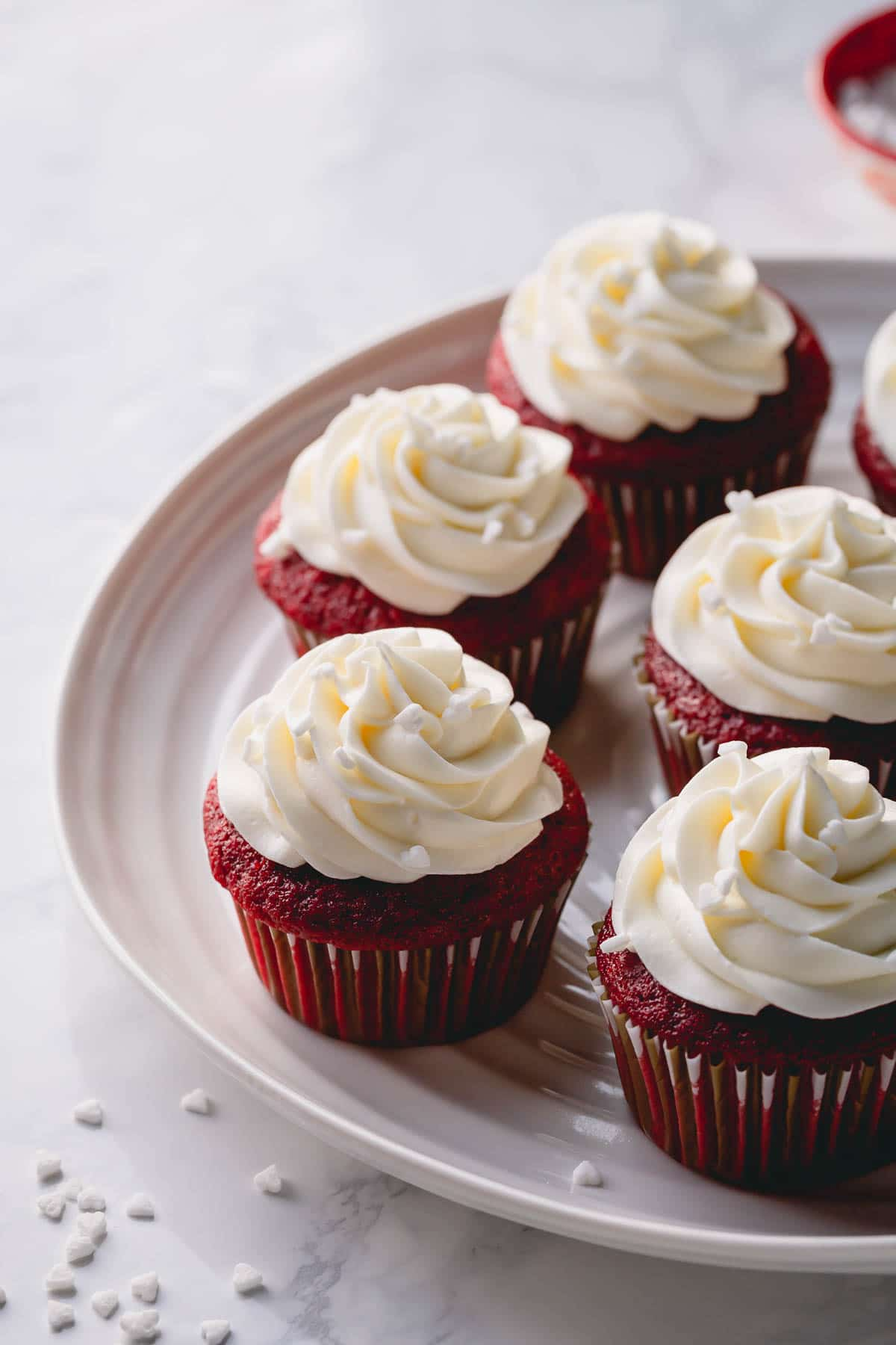 A platter of red velvet cupcakes with tall cream cheese frosting.