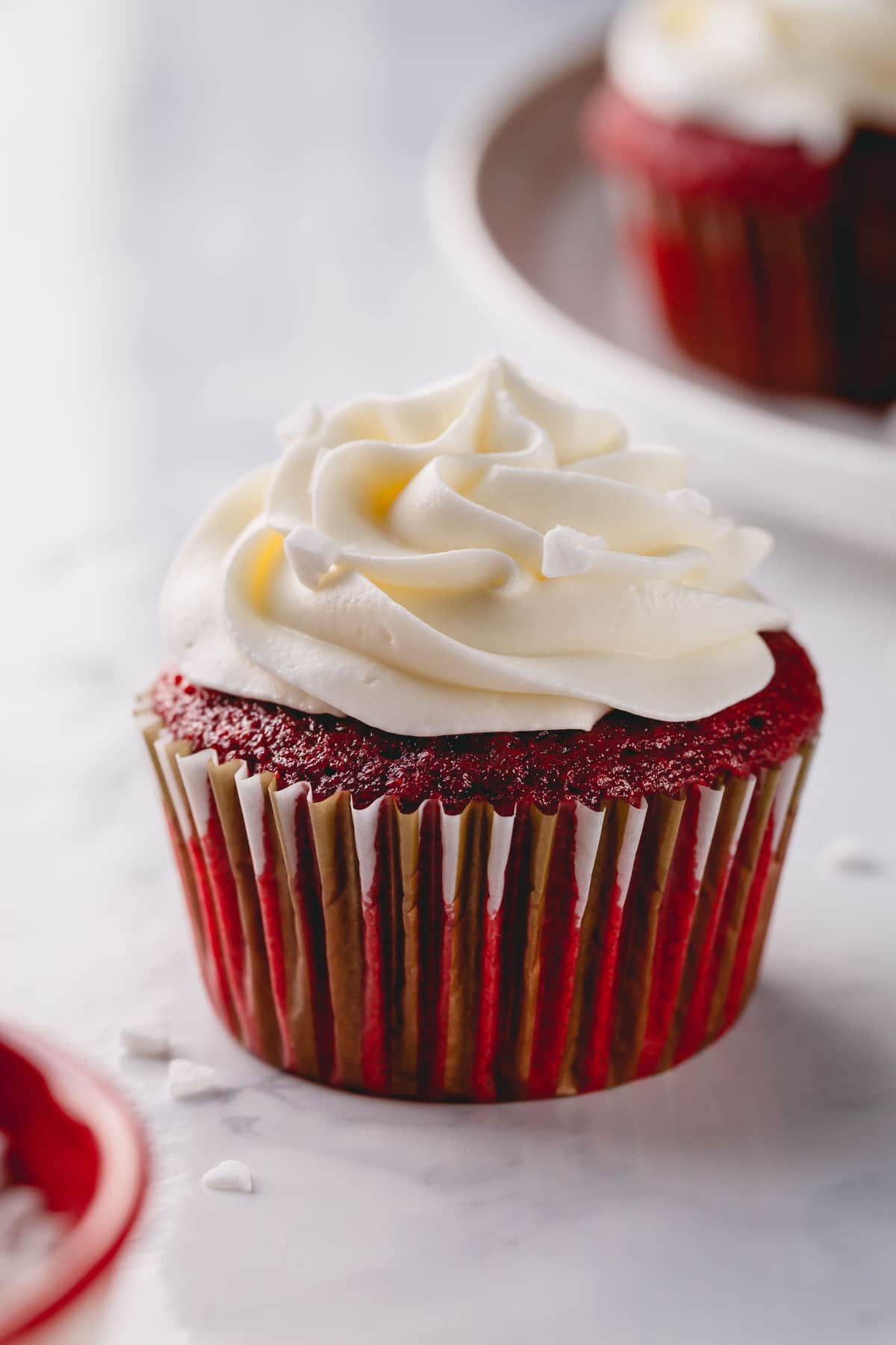 A red velvet cupcake with tall cream cheese frosting.